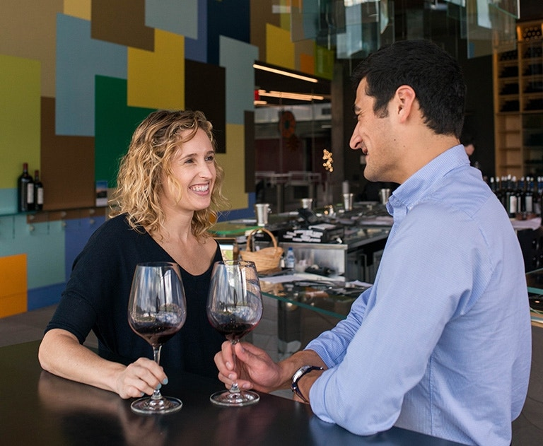 The Art of Cabernet on 2nd floor inside the tasting room with a man and woman enjoying Cabernet wine in glasses image