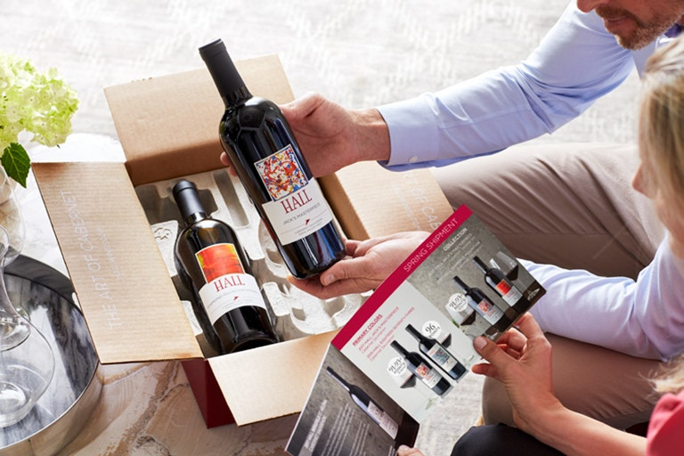 Tenure benefits image of two people opening wine club shipment package image